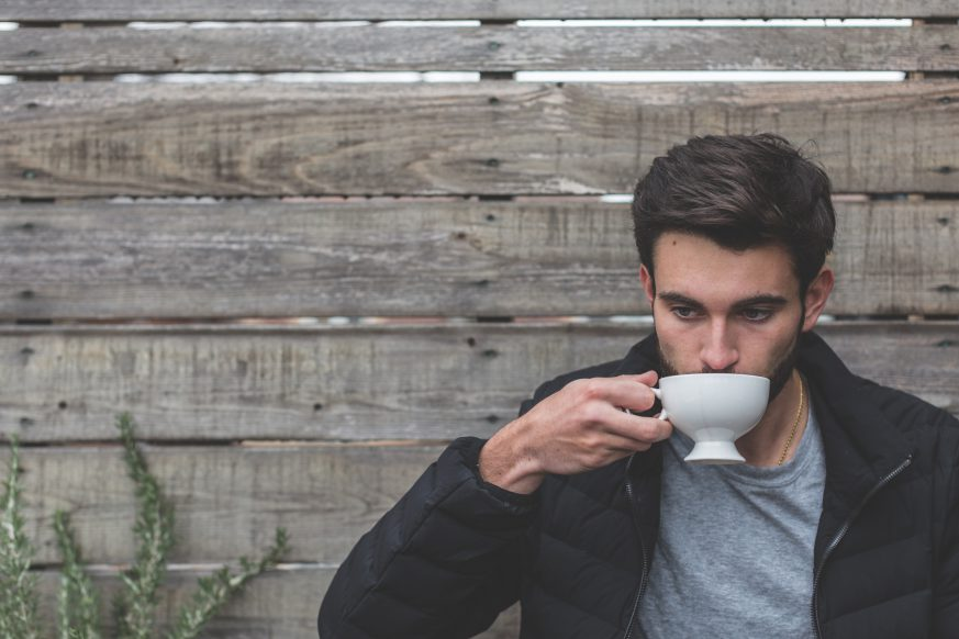 man drinking coffee which could impact adrenal health.